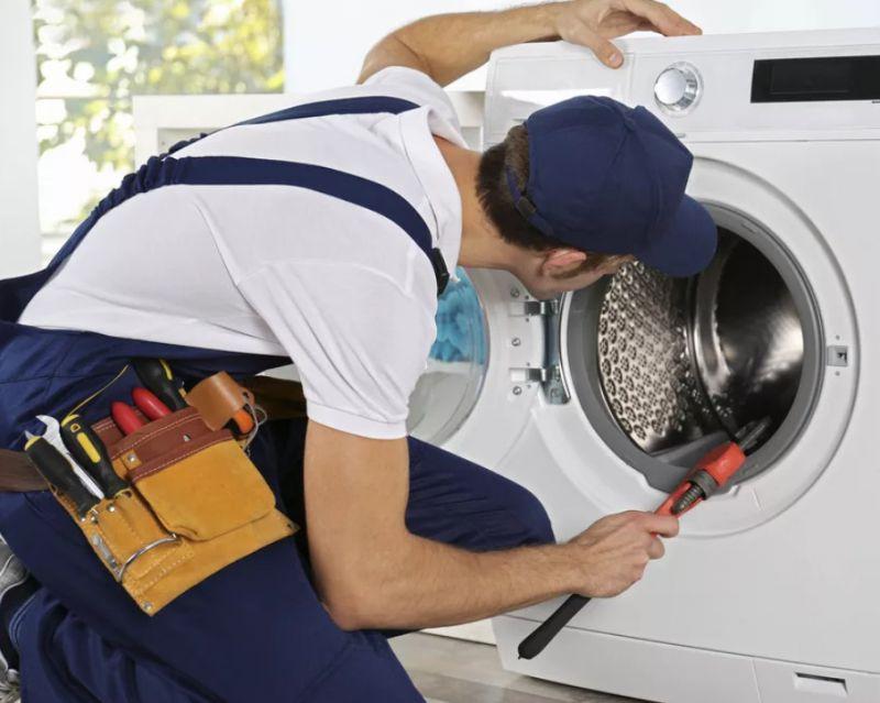 Мастер заглядывает в бак стиральной машины