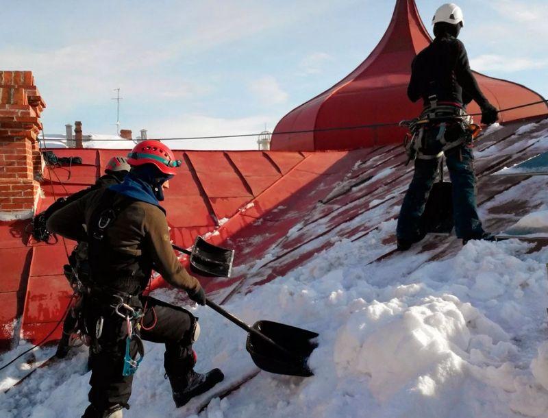 Работники расчищают крышу от наледи