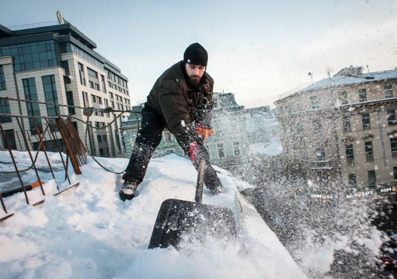 Рабочий очищает крышу от снега